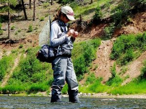 woman wearing fly fishing gear in vail valley