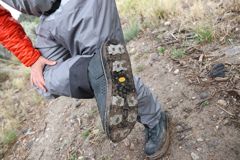 fisherman using patagonia wading boots and looking at the tread